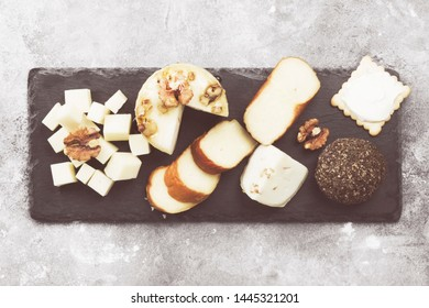 Various types of cheese on a gray background. Top view. Food background. Toned