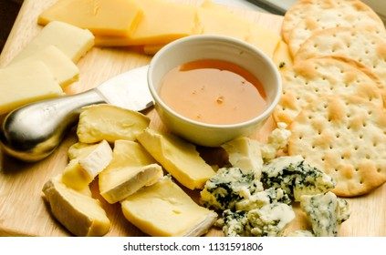various types of cheese on rustic wooden table,Cheese plate served with honey and crackers  on a wooden background