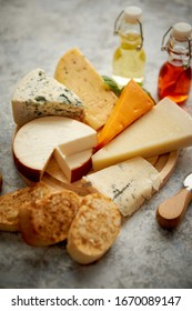 Verschiedene Käsearten werden auf rustikalem Holzbrett serviert. Auf betoniertem Hintergrund.