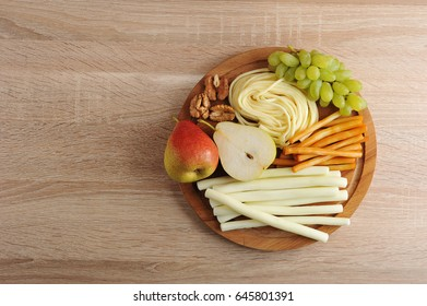 various types of cheese Suluguni cheese on a wooden plate with grapes, pear and walnuts - top view