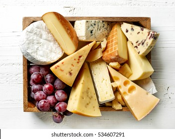 various types of cheese in wooden box on white wooden table, top view
