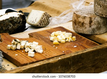 Various types of cheeses, on wooden cutting board, and rustic table in outdoor market.