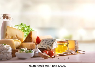 Various types of cheeses presented on a white wooden table in kitchen. Front view. Horizontal composition