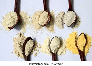 Various types of flour in vintage wooden spoons on white background