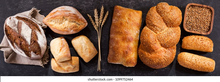 various types of fresh bread with wheat ears on dark table, top view