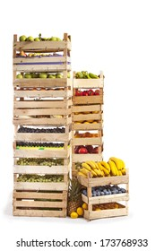 Various types of fruit and vegetables stored in wooden crates isolated