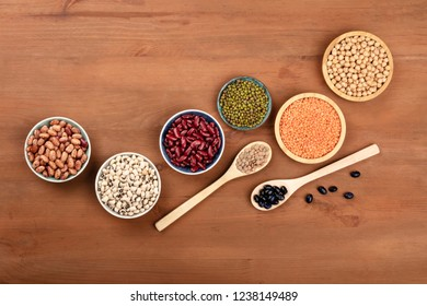 Various types of legumes, shot from above on a dark rustic wooden background. Red kidney beans, lentils, chickpeas, pinto beans, soybeans, black-eyed peas with a place for text