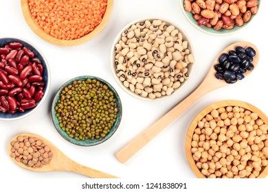 Various types of legumes, shot from above on a white background. Red kidney and pinto beans, lentils, chickpeas, soybeans, black-eyed peas