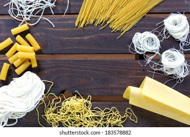 Various types of noodles and pasta cornered on wooden background