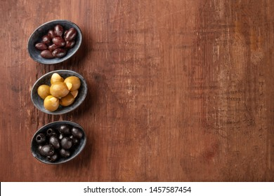 Various types of olives in bowls, overhead shot on a dark rustic wooden background with copy space. Purple, green almond stuffed, and black pitted olives with a place for text