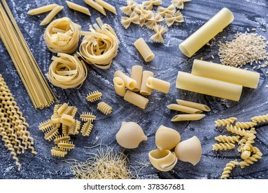 Various types of pasta on the dark flour dusted background