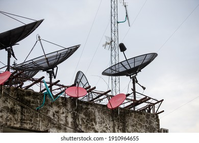 Various types of satellite dishes for watching television are located on the building's rooftop. Wireless technology.