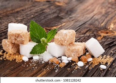 Various types of sugar and artificial sweetener on nwooden table.
