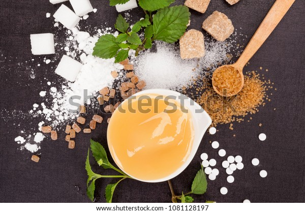 Various types of sugar  and artificial sweeteners with honey in bowl from above.