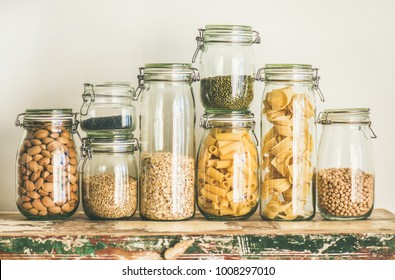 Various uncooked cereals, grains, beans and pasta for healthy cooking in glass jars on wooden table, white background, horizontal composition. Clean eating, vegan, balanced dieting food concept