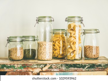 Various uncooked cereals, grains, beans and pasta for healthy cooking in glass jars on rustic table, white background. Clean eating, vegetarian, vegan, balanced dieting food concept