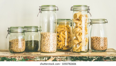Various uncooked cereals, grains, beans and pasta for healthy cooking in glass jars on rustic table, white background, wide composition. Clean eating, vegetarian, vegan, balanced dieting food concept