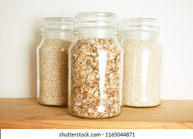 Various uncooked cereals, grains, and pasta for healthy cooking in glass jars on wooden table. Top view. Clean eating, balanced dieting food