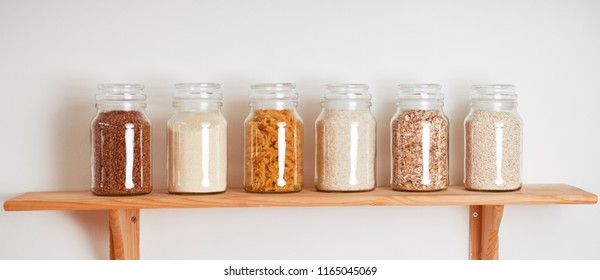Various uncooked cereals, grains, and pasta for healthy cooking in glass jars on wooden table. Top view. Clean eating, balanced dieting food. Banner.