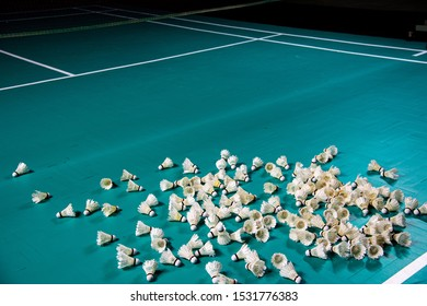 Various used Badminton shuttlecocks left on empty green Badminton court background.