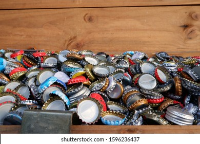 Various used bottle caps in a wooden crate. Close-up shot with copy space.