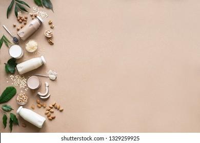 Various vegan plant based milk and ingredients on beige, top view, copy space. Dairy free milk substitute drink, healthy eating.