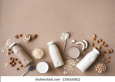Various vegan plant based milk and ingredients, top view, copy space. Dairy free milk substitute drink, healthy eating.