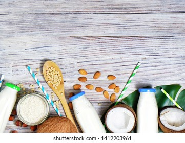 Various vegan plant based milk and ingredients on grey, top view, copy space. Dairy free milk substitute drink, healthy eating.