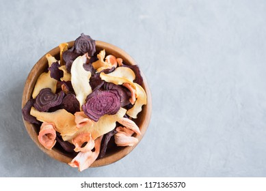 Various vegetable chips on grey background, copy space. Assorted dehydrated beetroot, carrot, pumpkin vegetable chips - healthy vegan snack.