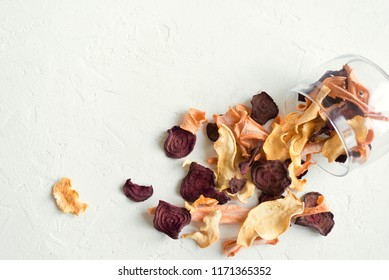 Various vegetable chips on white background, copy space. Assorted dehydrated beetroot, carrot, pumpkin vegetable chips - healthy vegan snack.