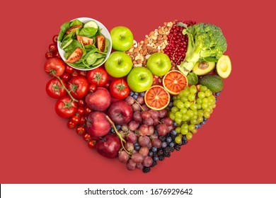 Various vegetables, fruit, nuts in heart shape on red background with clipping path. Selection of food for healthy heart and cardiovascular system, healthy diet and nutrition concept, top view