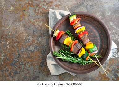 Various vegetables and meat kebabs on a dark plate, view from above