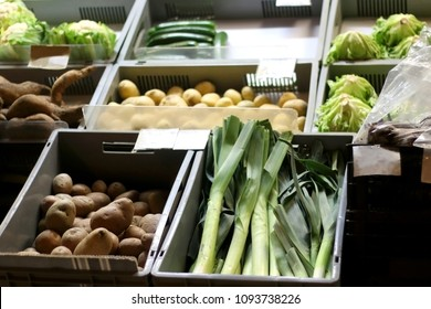 Various vegetables for sale on a market: leek, potato, salad, cabbage and zucchini. Selective focus.