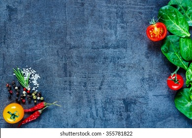 Various vegetarian ingredients (spinach, tomatoes, spices and herbs) on dark vintage table, top view. Healthy food, vegan or diet nutrition concept. Background layout with free text space.