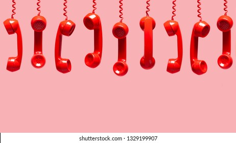 Various views of old red telephone receivers hanging on pink background with texting space, waiting for phone call, customer service concept, vintage telephone receiver