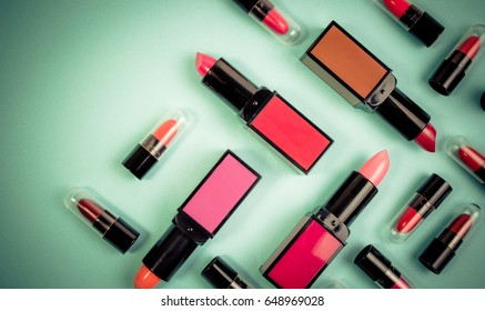 Various of vivid color lipstick make up on pastel green effect vintage background. Lipstick background with copyspace for text.