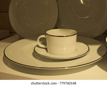 Various white porcelain cups, plates and teapots on a shelf in dishware shop