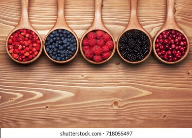 Various wild berries in small scoops on the wooden table. Background with space for text.