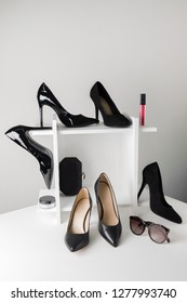 Various women high heels shoes on grey background. Black shoes in different material. Fashion accessories.