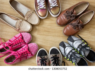 Various women's shoes and sneakers stand in the form of a circle with a free space in the middle, on a wooden background.