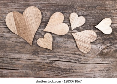 Various wooden hearts on a wooden background