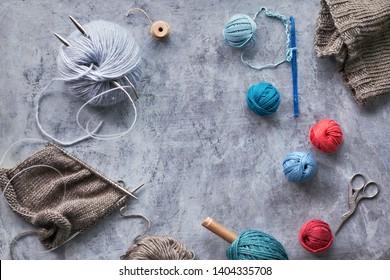 Various wool yarn and knitting needles, creative knitting hobby background