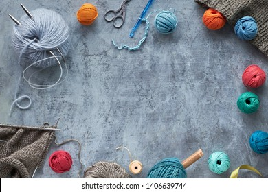 Various wool yarn and knitting needles, dark creative knitting hobby background with copy-space
