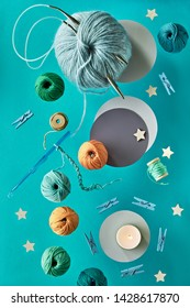 Various wool yarn and knitting needles, creative knitting hobby background in pastel colors on paper with copy-space