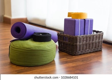 Various yoga props on studio wood floor. Set of blocks in wicker basket, belts, mat and green cushion in yoga center. Wellness activity concept