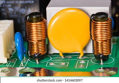 Varistor, inductors, capacitor and relay on green circuit board. Cylindrical induction coils with ferrite core, copper wire winding. Electro background with copy space on yellow round electronic part.