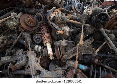 Varius car parts like shock absorbers, brake discs, axles, brakes and other parts. Stacked in an unarranged order. Awaiting recycling or re-sale. At a car cemetery. Kozani, Greece.