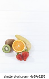 varius type of fruit with white wooden background with space for text (orange, kiwi, banana and strawberry) different healthy fruits