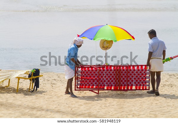 VARKALA, INDIA - JAN 05, 2017: Unidentified Indian workers with lounger on beach in Varkala. Kerala. India