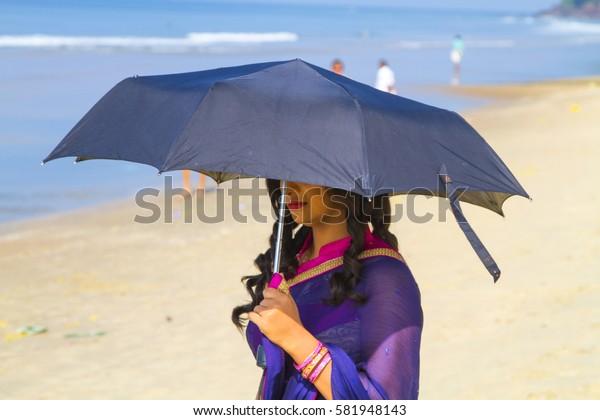 VARKALA, INDIA - JAN 05, 2017: Actress with umbrella goes to filming of music clip in Varkala. Kerala. India